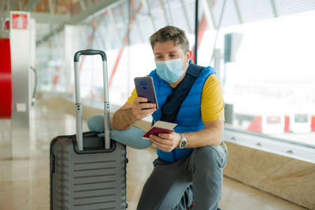 holiday travel and tourism  - young happy and attractive man in face mask at airport departures lounge checking mobile phone holding passport and boarding pass