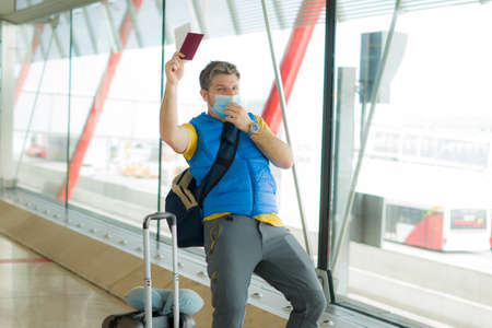 holiday travel and tourism   - young happy and attractive man in face mask at airport departures lounge holding passport and boarding pass