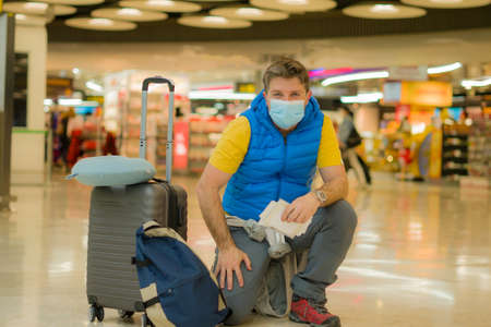 holiday travel and tourism during covid19 - young happy and attractive man in face mask at airport departures lounge holding passport and boarding pass Фото со стока