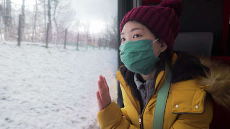 travel during  - young happy and beautiful Asian Chinese woman in face mask looking to snow through train window traveling during winter holiday