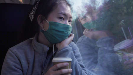 travel during  - young happy and beautiful Asian Chinese woman in face mask looking through train window traveling during winter holiday