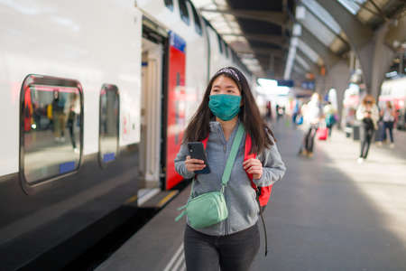 Asian backpacker girl traveling in times  - young happy and beautiful Chinese woman in face mask and backpack waiting for train at station platform visiting Europe Фото со стока