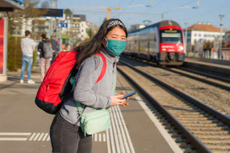 Asian backpacker girl traveling in times - young happy and beautiful Korean woman in face mask and backpack waiting for train at station platform visiting Europe