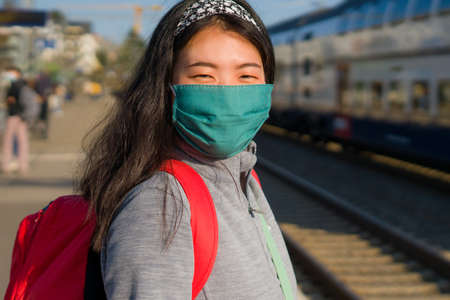 Asian backpacker girl traveling in times - young happy and beautiful Chinese woman in face mask and backpack waiting for train at station platform visiting Europe