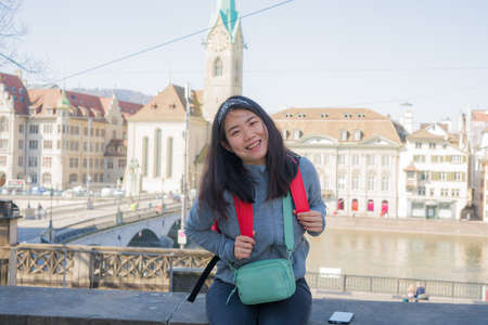 Asian woman backpacker touring in Europe - young happy and pretty Korean girl with backpack having city and river view from bridge during holidays in Europe Imagens