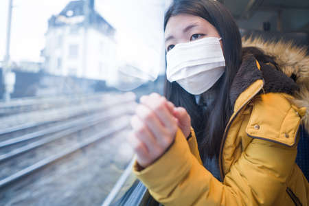 lifestyle portrait of young beautiful and thoughtful Asian Chinese woman in face mask as protection vs  looking through window during train trip
