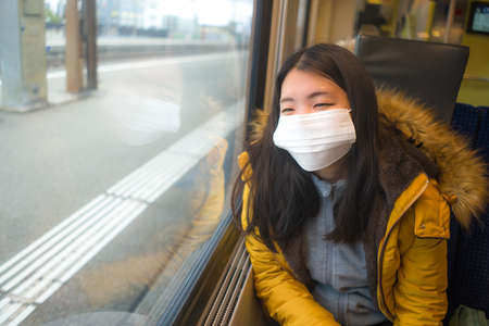 lifestyle portrait of young beautiful and thoughtful Asian Japanese woman in face mask as protection vs  looking through window during train trip