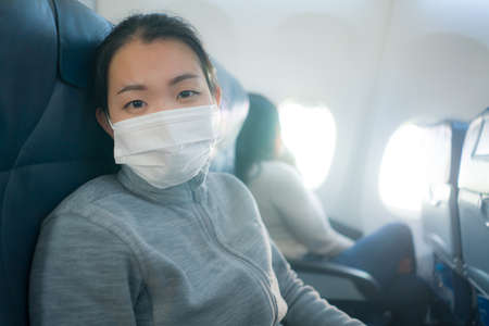 Asian tourist woman flying in times  - young happy and excited Korean girl in face mask sitting on airplane cabin ready for flight  looking at the camera