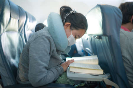 flying in times - young sweet and cute Asian Chinese woman in face mask sitting on airplane cabin reading book or novel enjoying the flight