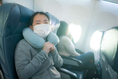 flying in times - young happy and excited Asian Korean woman in face mask sitting on airplane cabin ready for flight smiling cheerful Фото со стока