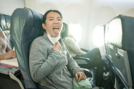 Asian tourist woman flying in times - young happy and funny Korean girl pulling off mask breathing free on airplane cabin ready for flight
