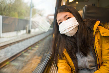 lifestyle portrait of young beautiful and thoughtful Asian Chinese woman in face mask as protection vs looking through window during train trip Фото со стока