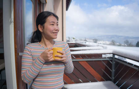 winter morning coffee - young happy and attractive Asian Chinese woman at hotel or home balcony in the snow drinking coffee looking away enjoying relaxed Фото со стока