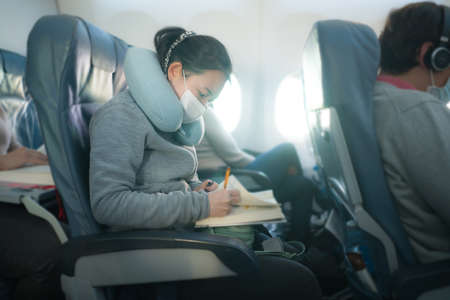 flying in times  - young sweet and cute Asian Korean woman in face mask sitting on airplane cabin reading book or novel enjoying the flight