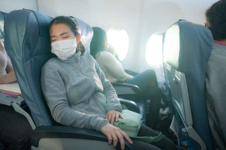 tourism and flying in times - young sweet and tired Asian Japanese woman in face mask sitting on airplane cabin sleeping peacefully during flight Standard-Bild