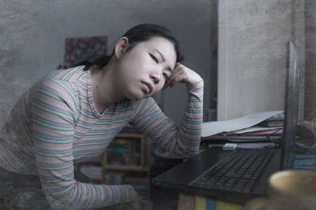 lifestyle portrait of young stressed and worried Asian Chinese woman working from home or studying exam in stress at home office feeling frustrated and tired Фото со стока