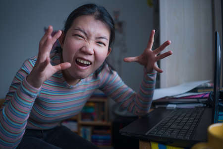 lifestyle portrait of young stressed and worried Asian Japanese woman working from home or studying exam in stress at home office feeling frustrated and tired