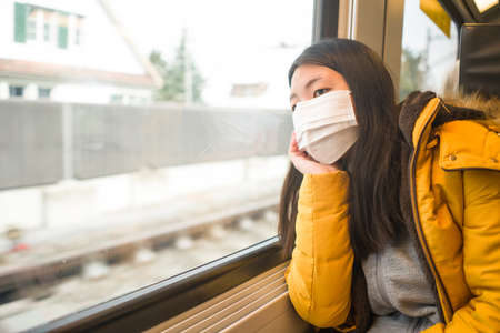 lifestyle portrait of young beautiful and thoughtful Asian Korean woman in face mask as protection vs looking through window during train trip