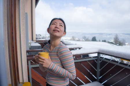 winter morning coffee - young happy and attractive Asian Korean woman at hotel or home balcony in the snow drinking coffee looking away enjoying relaxed