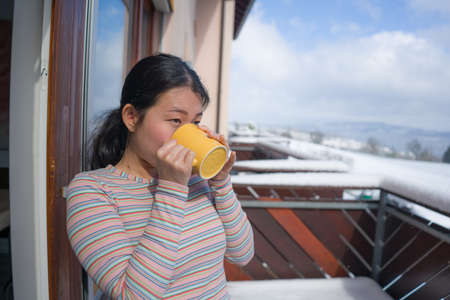winter morning coffee - young happy and attractive Asian Japanese woman at hotel or home balcony in the snow drinking coffee looking away enjoying relaxed Фото со стока