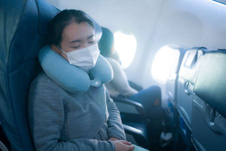 tourism and flying in times  - young sweet and tired Asian Chinese woman in face mask sitting on airplane cabin sleeping peacefully during flight