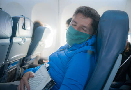 travel and tourism in times - lifestyle portrait of young attractive Caucasian man in face mask and neck pillow sleeping in airplane during flight