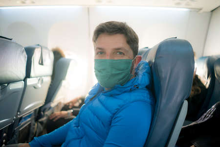 travel and tourism in times - lifestyle portrait of young attractive Caucasian man in face mask relaxed and cheerful in airplane during flight