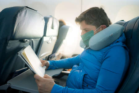 travel and tourism in times - lifestyle portrait of young attractive Caucasian man in face mask and neck pillow reading book in airplane during flight