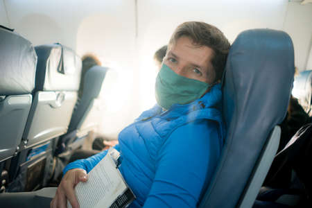 travel and tourism in times - lifestyle portrait of young attractive Caucasian man in face mask reading book in airplane during flight