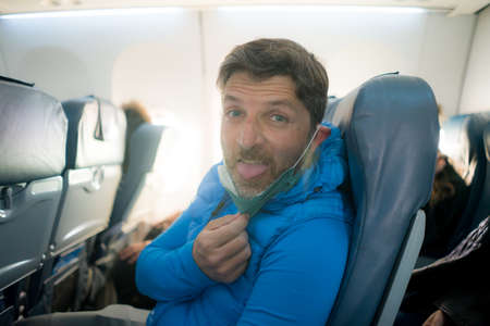 travel and tourism in times- lifestyle portrait of young attractive Caucasian man pulling off annoying and uncomfortable mask in airplane during flight