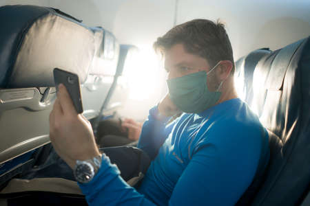travel and tourism in times - lifestyle portrait of young attractive Caucasian man in face mask using mobile phone in airplane during flight Фото со стока