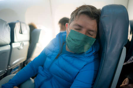 travel and tourism in times - lifestyle portrait of young attractive Caucasian man in face mask sleeping in airplane during flight Фото со стока