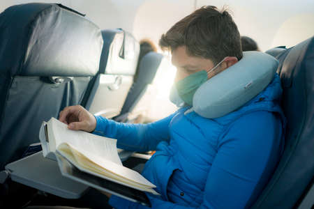 travel and tourism in times- lifestyle portrait of young attractive Caucasian man in face mask and neck pillow reading book in airplane during flight Фото со стока