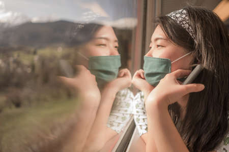 train travel in times- young happy and cute Asian Chinese woman in face mask traveling on rail car enjoying landscape through the window