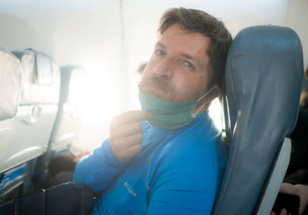 travel and tourism in times - lifestyle portrait of young attractive Caucasian man pulling off annoying and uncomfortable mask in airplane during flight