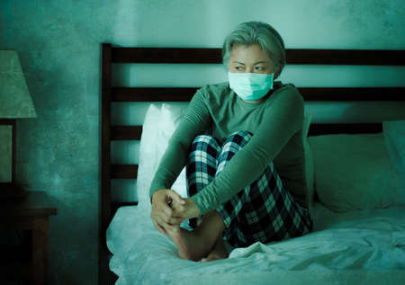 home dramatic portrait of  attractive middle aged woman 50s with grey hair and protective mask during covid-19 virus lockdown quarantine sitting on couch  thoughtful