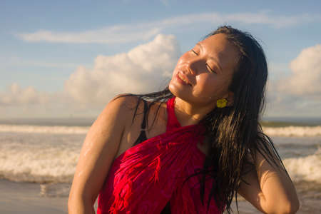 Summer lifestyle portrait of young happy and attractive Asian Chinese woman in traditional sarong at beautiful beach enjoying holiday trip to tropical island