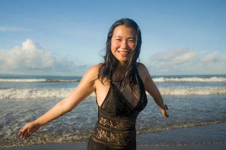 Summer lifestyle portrait of young happy and attractive Asian Japanese woman in bikini at beautiful beach enjoying holiday trip to tropical island