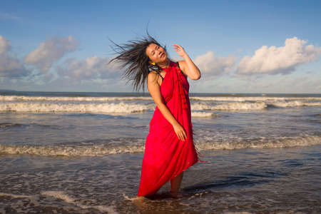 Summer lifestyle portrait of young happy and attractive Asian Korean woman in traditional sarong at beautiful beach enjoying holiday trip to tropical island