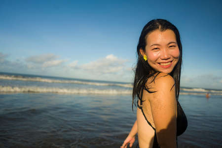 Summer lifestyle portrait of young happy and attractive Asian Korean woman in bikini at beautiful beach enjoying holiday trip to tropical island Foto de archivo