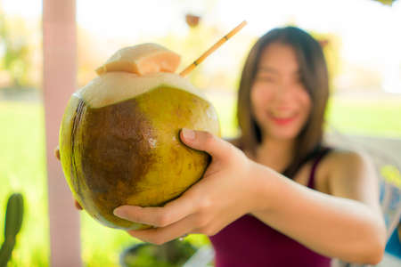 woman in shallow depth of focus holding young coconut happy and cheerful smiling outdoors enjoying the coconut water drink during summer holidays in Bali