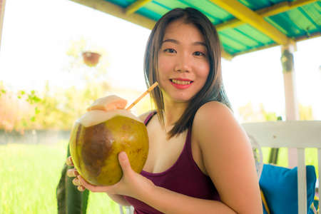 young happy and beautiful Asian Chinese woman holding young coconut drink outdoors smiling cheerful enjoying the coco water during Summer holidays