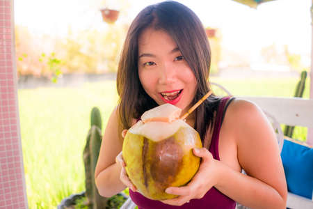 young happy and beautiful Asian Korean woman holding young coconut drink outdoors smiling cheerful enjoying the coco water during Summer holidays Foto de archivo