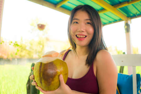young happy and beautiful Asian Japanese woman holding young coconut drink outdoors smiling cheerful enjoying the coco water during Summer holidays Foto de archivo