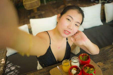 summertime lifestyle portrait of young attractive and happy Asian Chinese woman taking selfiei having healthy lunch with organic food and orange juice during holidays