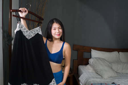 natural portrait of young happy and sweet Asian Korean woman trying different clothes  looking in bedroom mirror deciding what new dress for dating