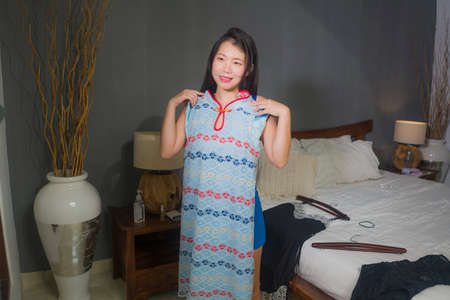 natural portrait of young happy and sweet Asian Chinese woman trying different clothes  looking in bedroom mirror deciding what new dress for dating