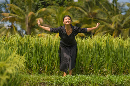 artistic portrait of young attractive and happy Asian woman outdoors at green rice field landscape dancing and doing relaxation body and mind yoga balance exercise