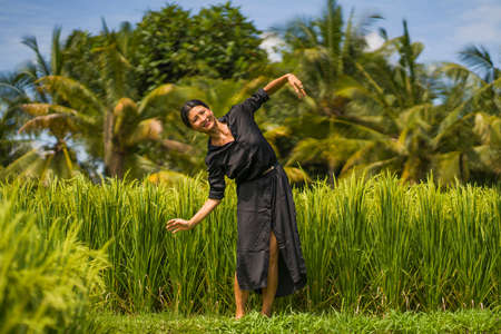 artistic portrait of young attractive and happy Asian woman outdoors at green rice field landscape wearing elegant long dress dancing on nature carefree