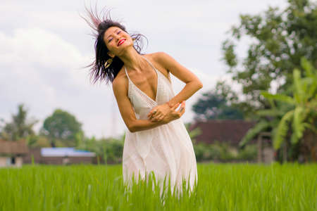 artistic portrait of young attractive and happy Asian woman outdoors at green rice field landscape wearing elegant long dress dancing on beautiful nature carefree